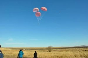 由三个降落伞组成的群伞正在缓慢下降