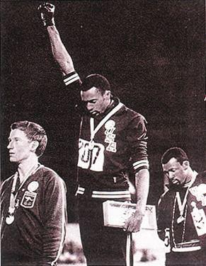 1968年墨西哥奥运会领奖台上,托米·史密斯(中)高举戴有黑色手套右拳。